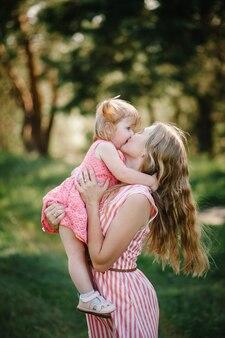 Retrato de una hija abrazando y besando a la madre en la naturaleza en las vacaciones de verano. mamá y niña jugando en el parque a la hora del atardecer. concepto de familia amistosa. de cerca.