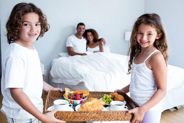 Retrato de hija e hijo llevando bandeja de desayuno para padres