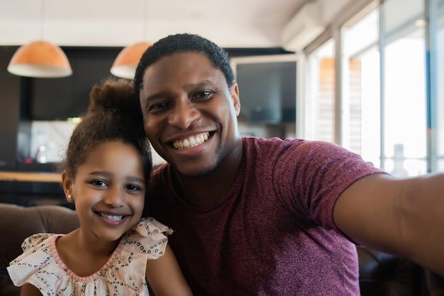 Retrato de una hija y un padre divirtiéndose juntos y tomando un selfie mientras está sentado en el sofá en casa