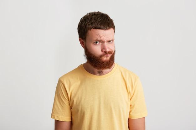 Retrato de hipster joven atractivo feliz con barba viste camiseta parece seguro y sospechoso