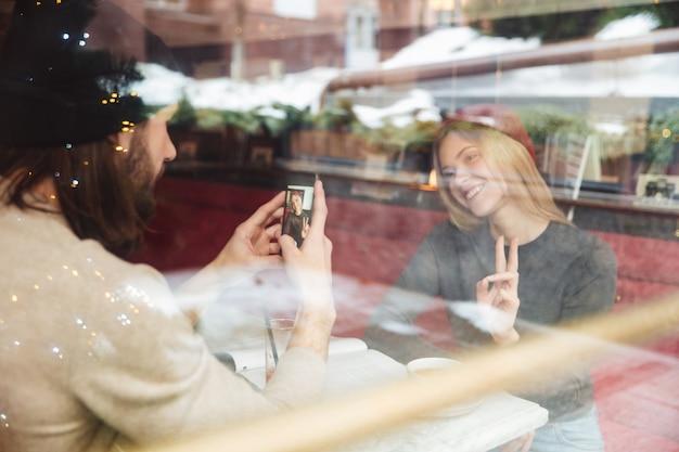 Retrato de hipsters haapy en café detrás del cristal