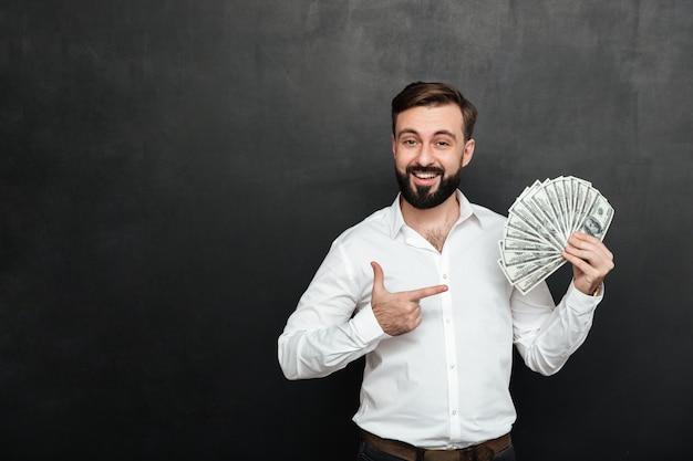 Retrato de hombre adulto en camisa blanca posando en cámara con abanico de billetes de 100 dólares en la mano, ser rico y feliz sobre gris oscuro