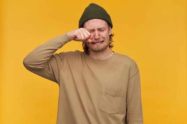 Retrato de hombre adulto desesperado con cabello rubio y barba. el uso de gorro verde y suéter beige. llora y se enjuga el ojo de las lágrimas. párese aislado sobre la pared amarilla