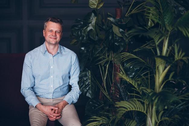 Retrato del hombre adulto medio mayor sonriente en camisa azul con la mirada de las plantas verdes. planta de jardinería doméstica.