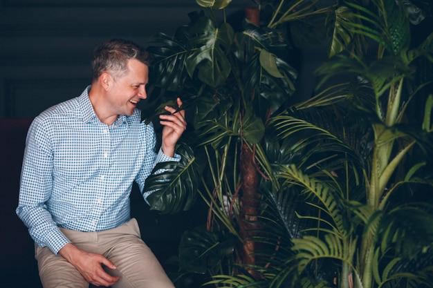 Retrato del hombre adulto medio mayor sonriente en camisa azul con las plantas verdes. planta de jardinería doméstica.