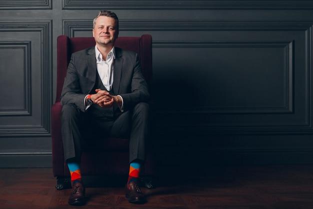 Retrato del hombre adulto medio mayor sonriente en traje gris y calcetines multicolores coloridos que miran la cámara con el espacio de la copia.