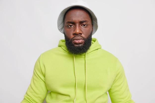 Retrato de hombre adulto serio tiene barba espesa viste panamá y sudadera casual verde mira directamente al frente aislado sobre pared blanca