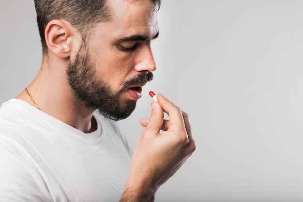 Retrato de hombre adulto tomando una pastilla