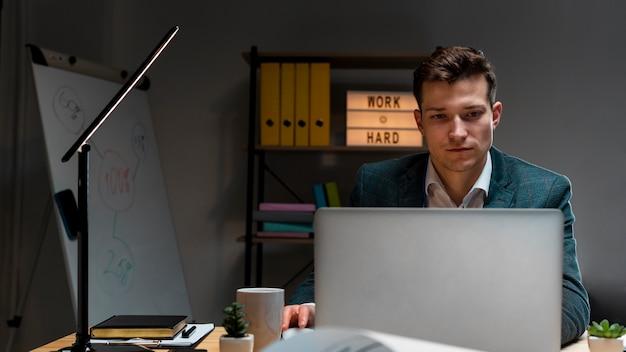 Retrato de hombre adulto trabajando remotamente en la noche