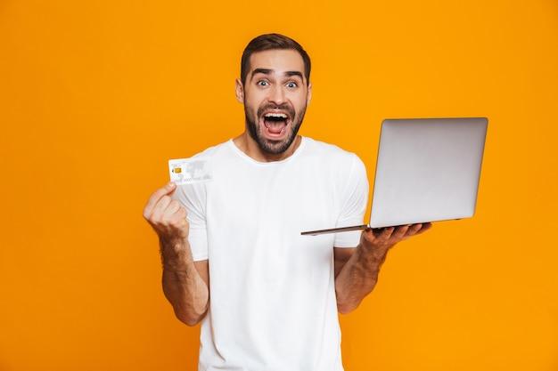Retrato de hombre sin afeitar de 30 años en camiseta blanca con portátil plateado y tarjeta de crédito, aislado