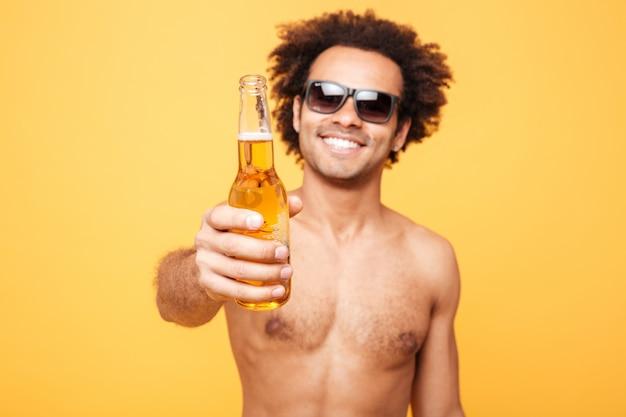 Retrato de un hombre africano en gafas de sol que muestra la botella de cerveza