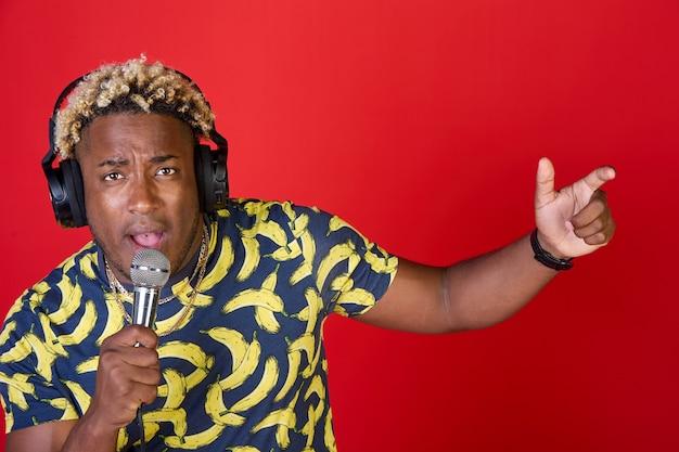 Retrato de un hombre africano hermoso disfrutando positivo con un micrófono y auriculares en la cabeza