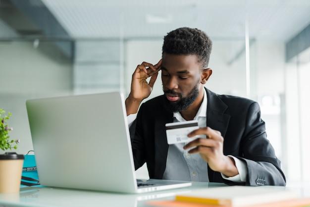 Retrato del hombre africano joven confidente que sostiene la tarjeta de crédito con la computadora portátil que paga vía internet