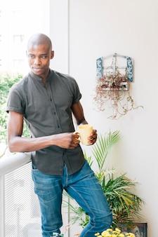Retrato de un hombre africano joven que se coloca en el balcón que se inclina en la verja que sostiene la taza de café