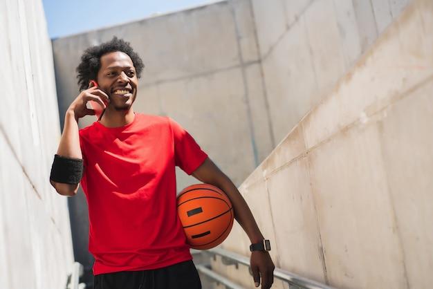 Retrato de hombre afro atleta hablando por teléfono y relajarse después de entrenar al aire libre. deporte y estilo de vida saludable.