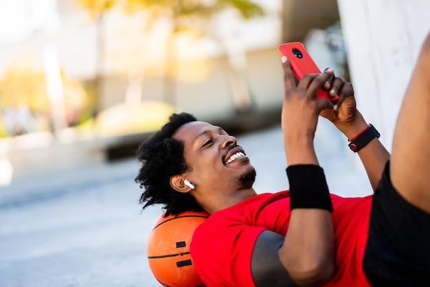 Retrato de hombre afro atleta usando su teléfono móvil mientras está acostado en el piso después de entrenar al aire libre. deporte y estilo de vida saludable.
