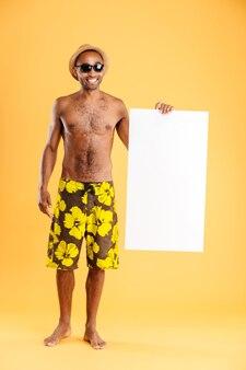 Retrato de un hombre afro feliz sosteniendo un tablero en blanco y mostrando un signo bien aislado en una pared naranja