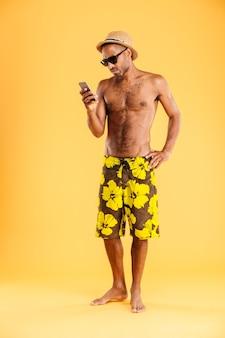 Retrato de un hombre afro pensativo hablando por teléfono aislado en una pared blanca