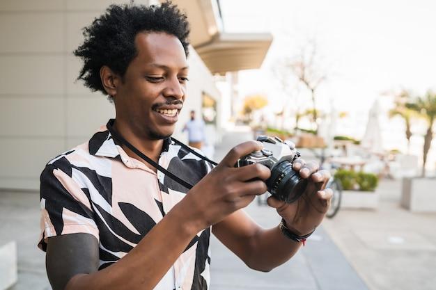 Retrato de hombre afro turista tomando fotografías con cámara mientras camina al aire libre en la calle. concepto de turismo.
