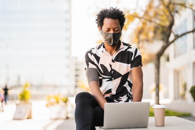 Retrato de hombre afro turista usando su computadora portátil y con máscara protectora mientras está sentado al aire libre. concepto de turismo. nuevo concepto de estilo de vida normal.