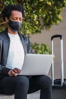 Retrato de hombre afro turista usando su computadora portátil y con máscara protectora mientras está sentado al aire libre. concepto de turismo.