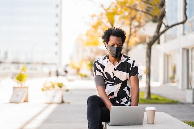 Retrato de hombre afro turista usando su computadora portátil y con máscara protectora mientras está sentado al aire libre.
