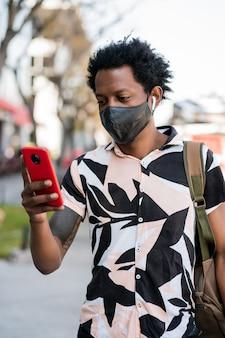 Retrato de hombre afro turista usando su teléfono móvil mientras camina al aire libre en la calle