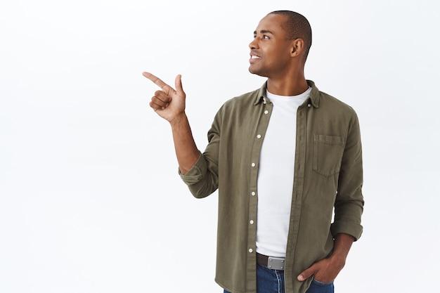 Retrato de hombre afroamericano adulto guapo en traje casual, gire la cabeza y señale con el dedo hacia la izquierda con una sonrisa complacida, recogiendo de la tabla