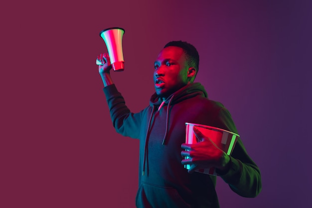 Retrato del hombre afroamericano aislado en gradiente de pared en luz de neón