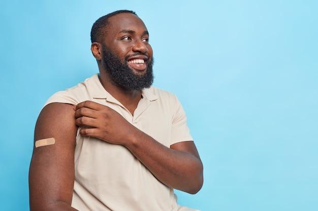 Retrato de hombre afroamericano barbudo alegre muestra el brazo con vendaje de yeso feliz de recibir la vacunación mira hacia otro lado y sonríe vestido con camiseta casual aislada sobre pared azul