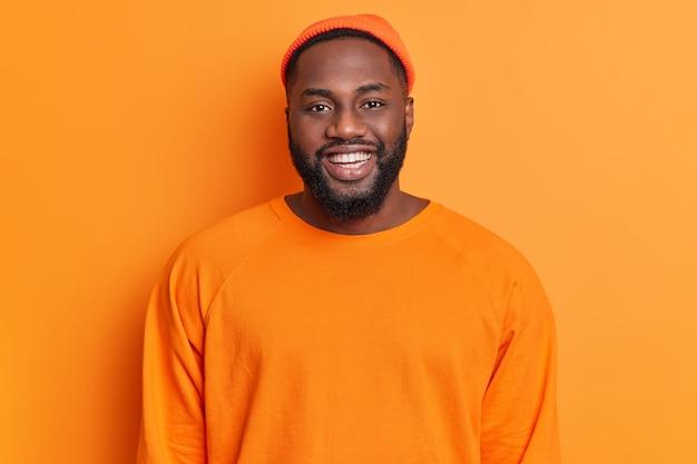 Retrato de hombre afroamericano barbudo alegre tiene expresión feliz sonríe ampliamente tiene dientes blancos perfectos