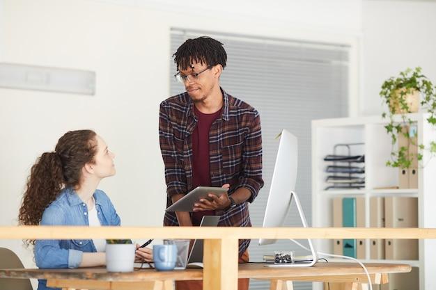 Retrato de hombre afroamericano contemporáneo hablando con colega y mostrando tableta digital mientras está de pie en el interior de la oficina blanca, espacio de copia