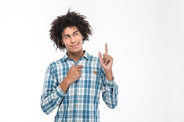 Retrato de un hombre afroamericano feliz apuntando con el dedo hacia arriba aislado en una pared blanca