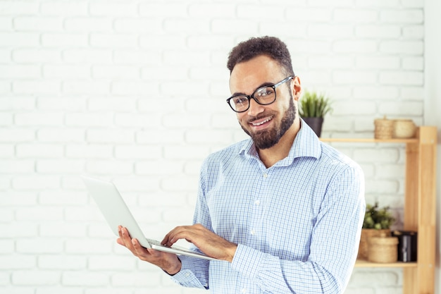 Retrato de hombre afroamericano feliz usando computadora portátil