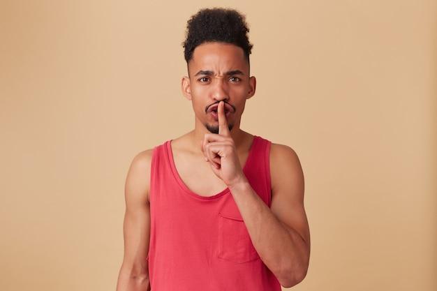 Retrato de hombre afroamericano infeliz con peinado afro y barba. llevaba camiseta roja sin mangas. enojado mostrando signo de silencio. fruncir el ceño, aislado sobre la pared beige pastel