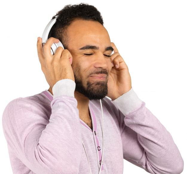 Retrato de un hombre afroamericano joven alegre que escucha la música con los auriculares