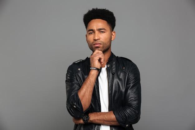 Retrato de un hombre afroamericano pensativo en chaqueta de cuero