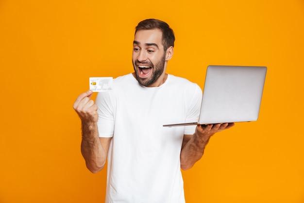 Retrato de hombre alegre de 30 años en camiseta blanca con portátil plateado y tarjeta de crédito, aislado