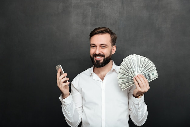 Retrato de hombre alegre en camisa blanca ganando mucho dinero en dólares usando su teléfono inteligente, siendo alegre sobre gris oscuro