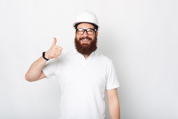 Retrato de hombre alegre joven arquitecto barbudo con gafas y mostrando el pulgar hacia arriba