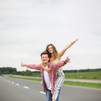 Retrato de un hombre alegre que lleva a su novia a su espalda y se divierte