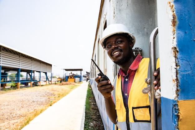 Retrato del hombre americano de áfrica sosteniendo la barandilla de ingeniería y con casco de desgaste en frente de la estación de tren