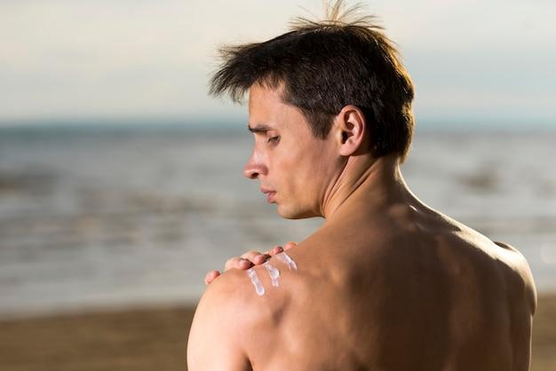 Retrato de un hombre aplicando loción de protección solar