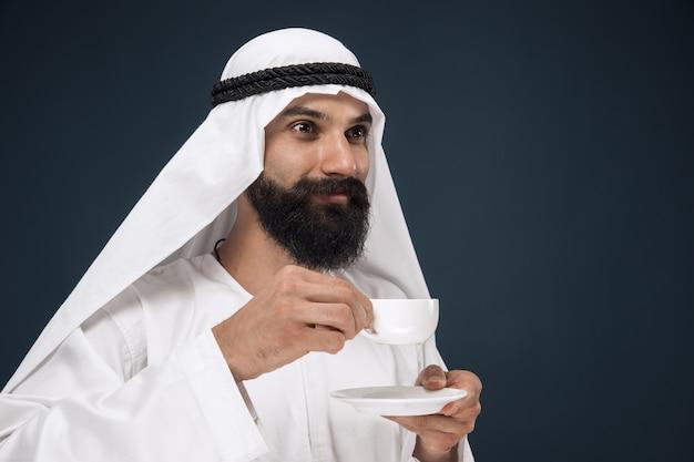 Retrato del hombre árabe saudí. modelo masculino joven de pie y bebiendo café o té.