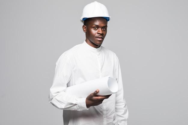 Retrato de hombre de arquitecto afroamericano confiado y sonriente con blueprint, mirando a la cámara aislada sobre fondo gris