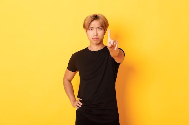 Retrato de hombre asiático decepcionado de aspecto serio agitando el dedo para regañar a alguien, de pie pared amarilla