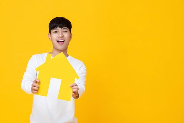 Retrato del hombre asiático feliz joven que sostiene el hogar de papel