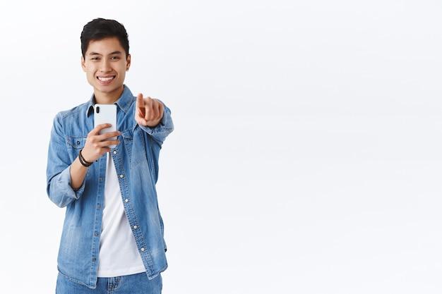 Retrato de hombre asiático guapo carismático que toma una foto o graba un video de usted, apunta al frente, sostiene el teléfono inteligente y sonríe entretenido, pared blanca