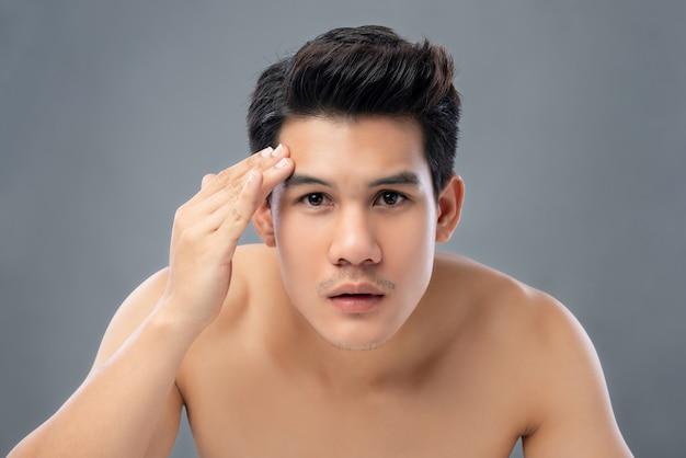 Retrato del hombre asiático hermoso joven descamisado que comprueba su piel de la cara