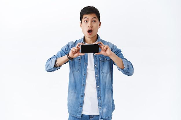 Retrato de hombre asiático impresionado joven asombrado que muestra el nuevo tráiler de la película en la pantalla del teléfono inteligente, sosteniendo el teléfono móvil horizontalmente, la boca abierta divertida